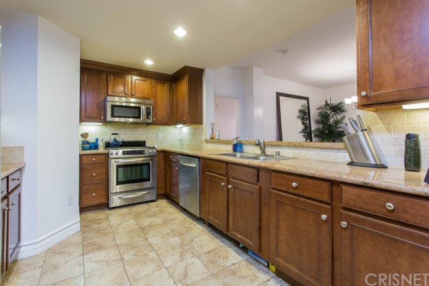Kitchen with Stainless Steel Appliances and Granite Counters. Kitchen opens to Formal Dining area and Living Room.