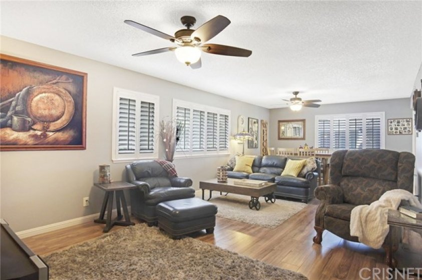 Living room and dining area with new hardwood floors, plantation shutters and ceiling fans