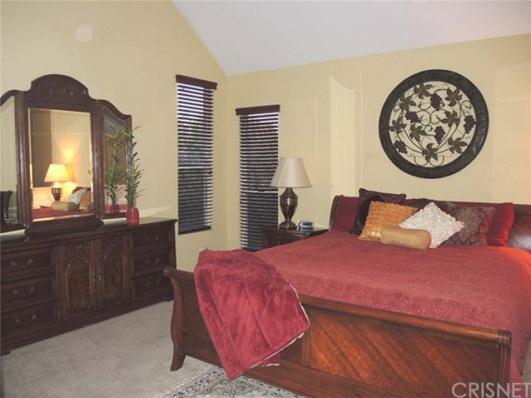 Step-up oversized master bedroom with soaring ceiling, architectural details, raised fireplace