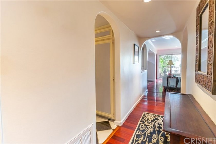 Entry to hallway. Recessed lighting, teak flooring, curved archways. (laundry room in opposite direction not pictured).