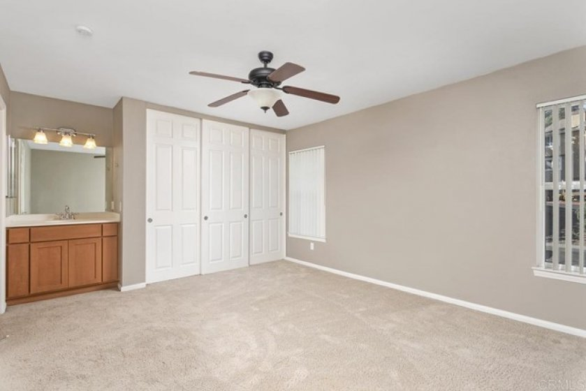 Large Master Bedroom with Vanity and Fan.  Sliding Closet Doors for Big Closet