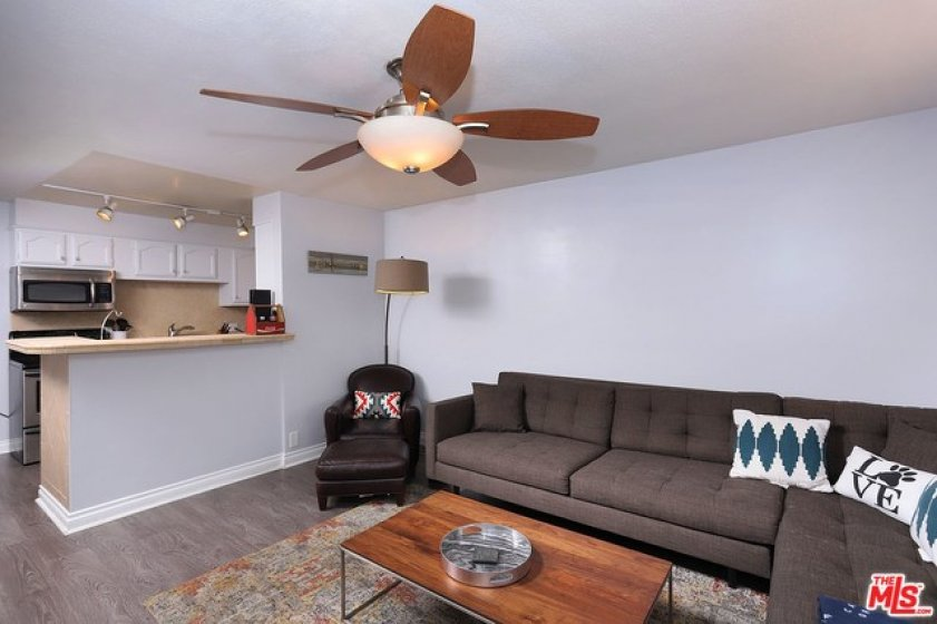 Living room to kitchen - ceiling fan, counter top seating.
