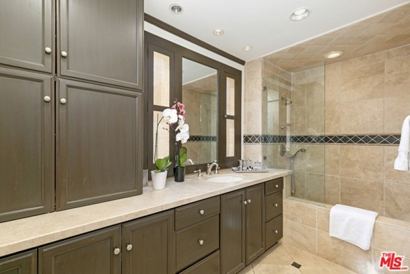 Light filled bathroom with built-ins and a private commode area