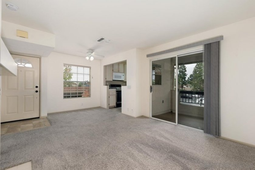 Living/dining area with fireplace and leads towards your tree-lined balcony deck.