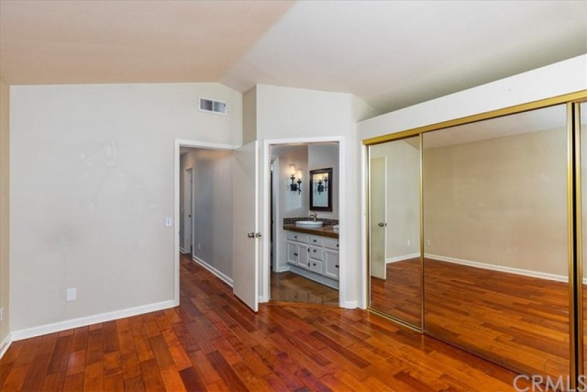 Master bedroom with mirrored closet doors.  Adjoining remodeled master bath with dual basins.