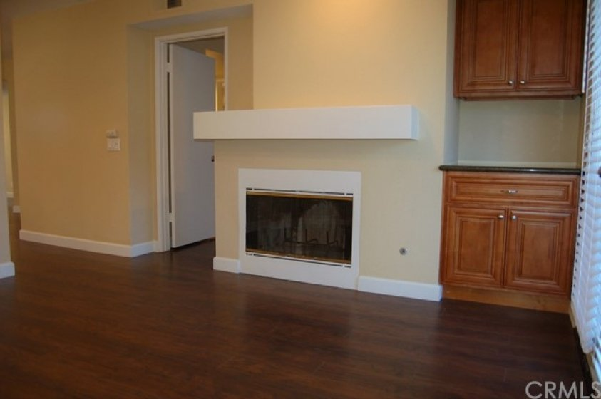 Living room with fireplace, granite counter on newer cabinets and French doors that lead to the very private backyard.