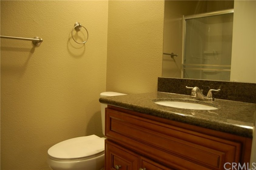 Secondary bathroom has the same flooring and granite counter tops. There is a shower with a raised shower head over a tub with glass slider doors. Low flow toilet and recessed lighting add to this bathroom.