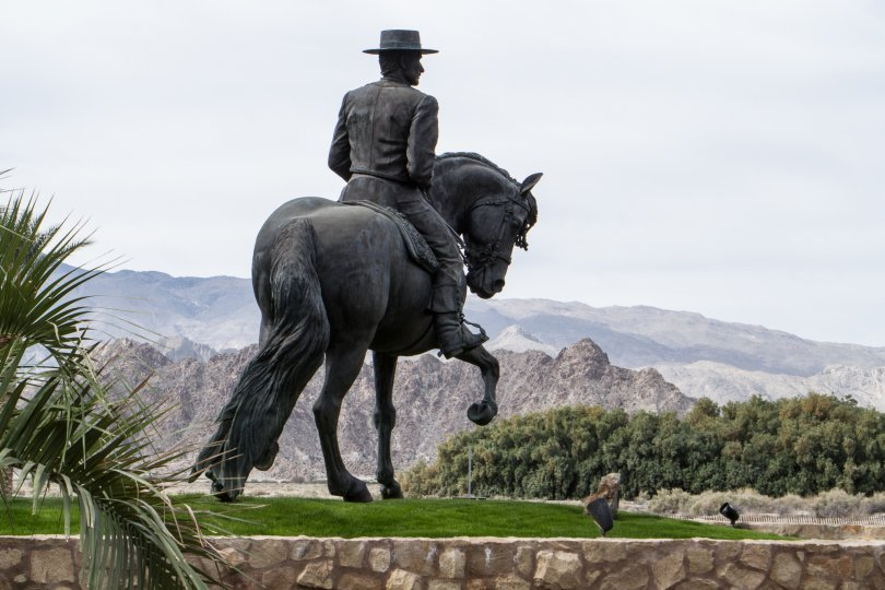 The Bronze statue sits at the entry of Andalusia Country Club overlooking the mountains in the background