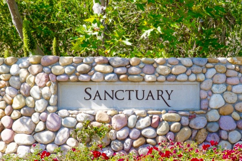 Sanctuary Community sign made of river rock and concrete