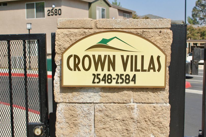 An emblem of a mountain sits on a sign at the Crown Villas community.