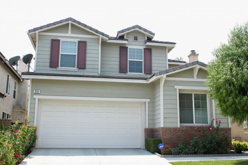 Front house with garage and rose bushes with beautiful tree and gardens