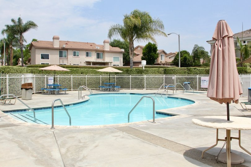 there is a large swimming pool at the front of house with table and chair is surrounded by trees and grasses