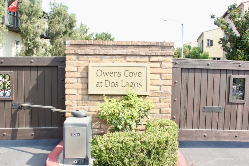 Close up of sign and gate of Owens Cove at Dos Lagos on Market Street in Corona, CA.