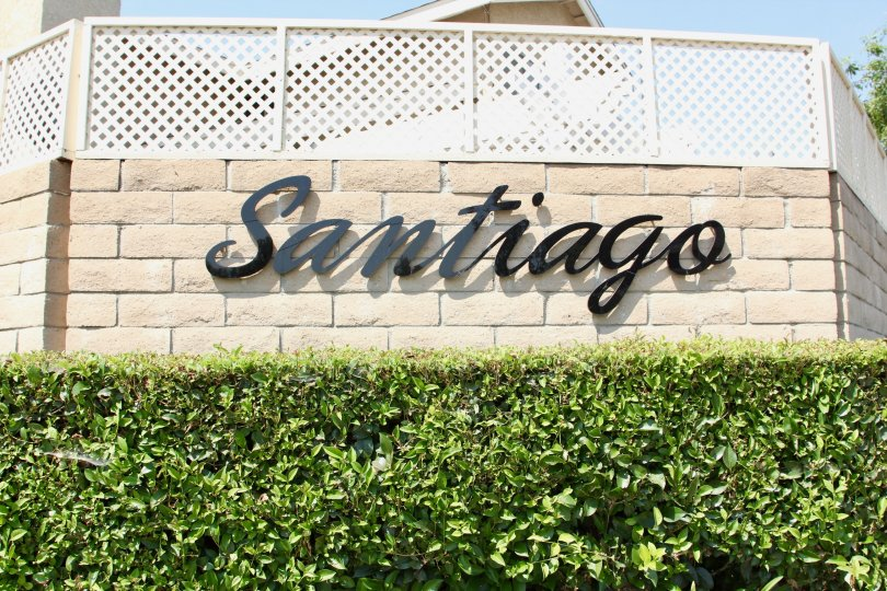 Hedges adorn this brick wall sign of Santiago with green hedges in sunlight