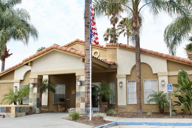 Front entrance, with flag and palmtrees outside the Sienna community in Corona, California