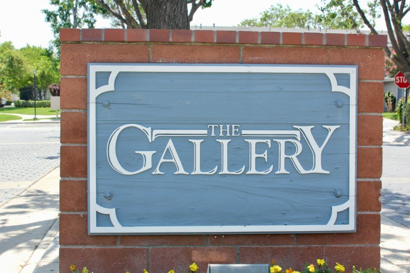 Entrance sign made of brick and blue background saying The Gallery with flowers planted and gardens in the distance