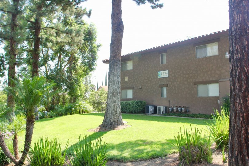 Apartment building and green lawn in The Lakes at Corona community of Corona, CA.
