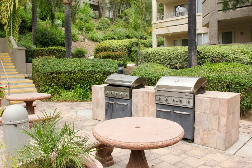 Two outdoor barbecue grills and seating on patio of Triana at Corona Ranch in Corona, CA.