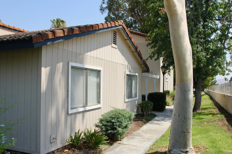 Side of a tan home with exterior side walkway in the Village Grove Cluster community of Corona, California