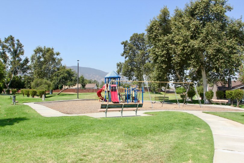 Childrens playground with slides, swing sets open grass, trees and picnic area with mountain view
