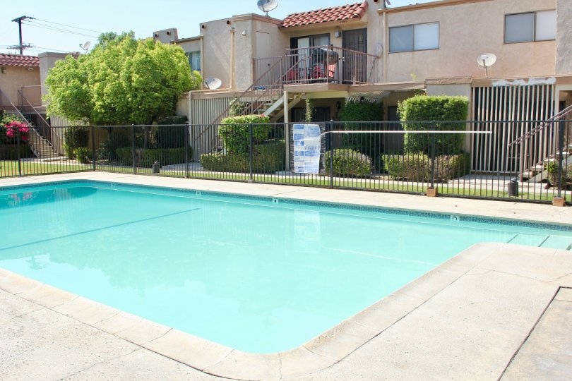 A clear day at an Acacia Gardens apartment complex and inground swimming pool in Hemet, CA.