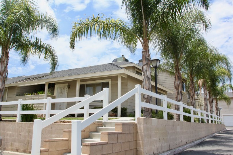 Palm trees line a white fence surrounding a ranch style home in the Lake Country Villas