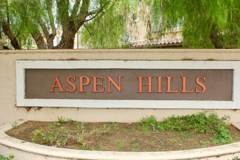 Cottonwoods surround the copper writing on the sign to the main entrance of Aspen Hills