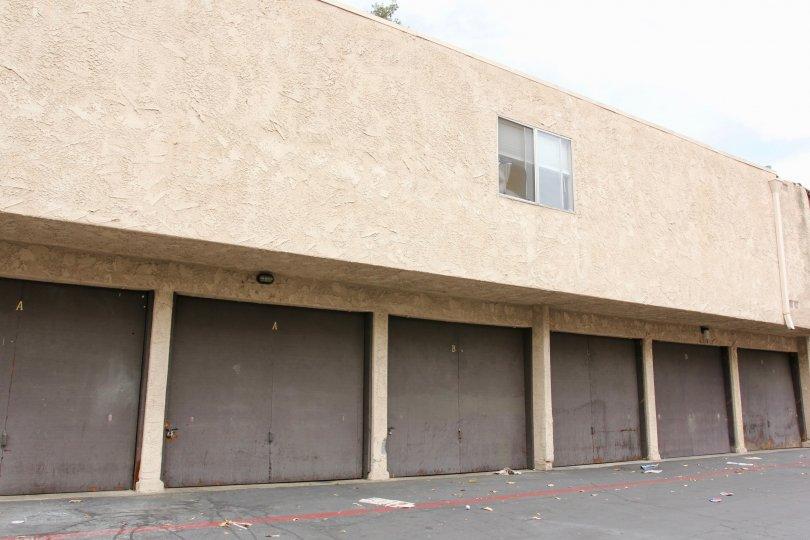 Rectangular apartment building with single window and brown garage doors