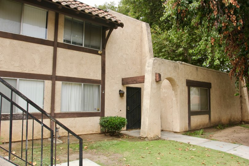 Spanish Pueblo looking architecture with shady grass and large trees
