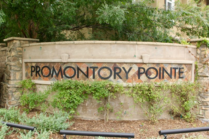 Promontory Pointe sign with leafy green vegetation in the daytime