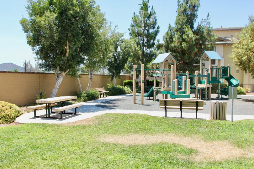 Childrens playground featuring picnic tables, benches and play equipment in Amberwalk at Ivy in Murrieta California