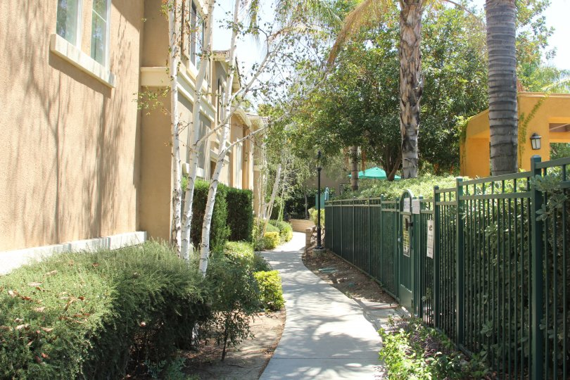Arboretum murrieta California tall building with long standing grill gates with narrow path and tall trees