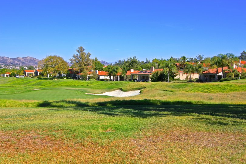 The golf course of the Bear Creek Villas community on a sunny day.