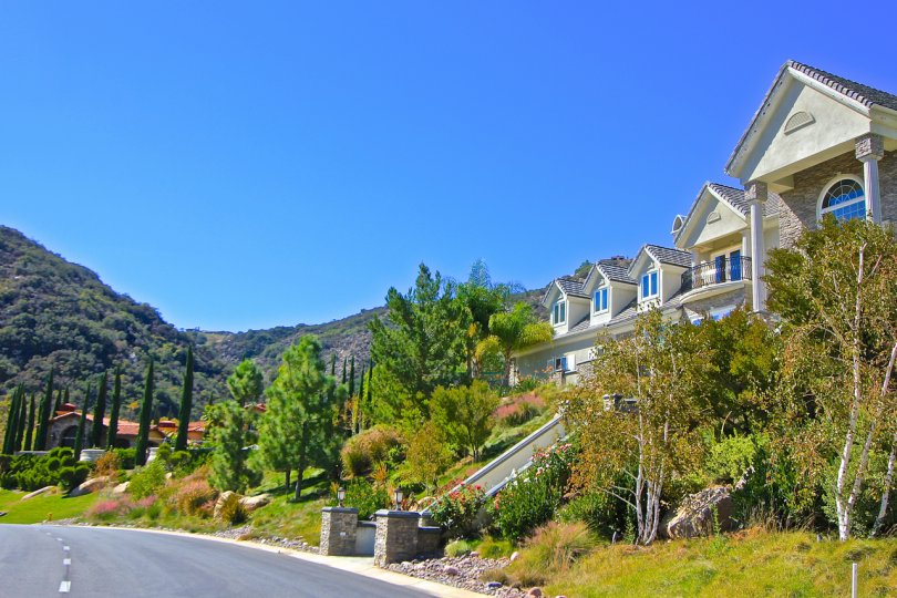 Street view of Bear Creek Villas with hills and trees on a perfectly clear day with blue skies in Murietta, CA.