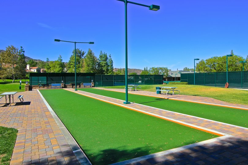 Bocce balls courts with park benches under brilliant blue skies