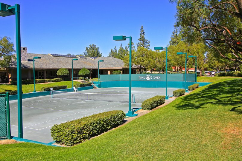 A teal green fence surrounds a tennis court at the Fairway Estates at Bear Creek.