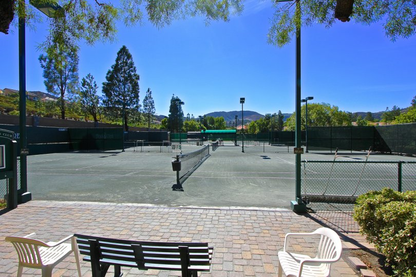 Tennis courts with a mountain view with trees in the distance on this sunny day