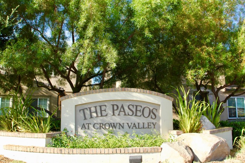 The paseos at crown valley is written on a sign in a garden