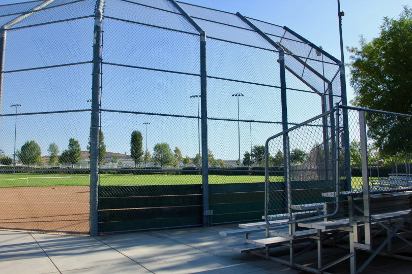 Shaded bleachers await behind home plate at the park by Paseos at Crown Valley in Murrieta, CA