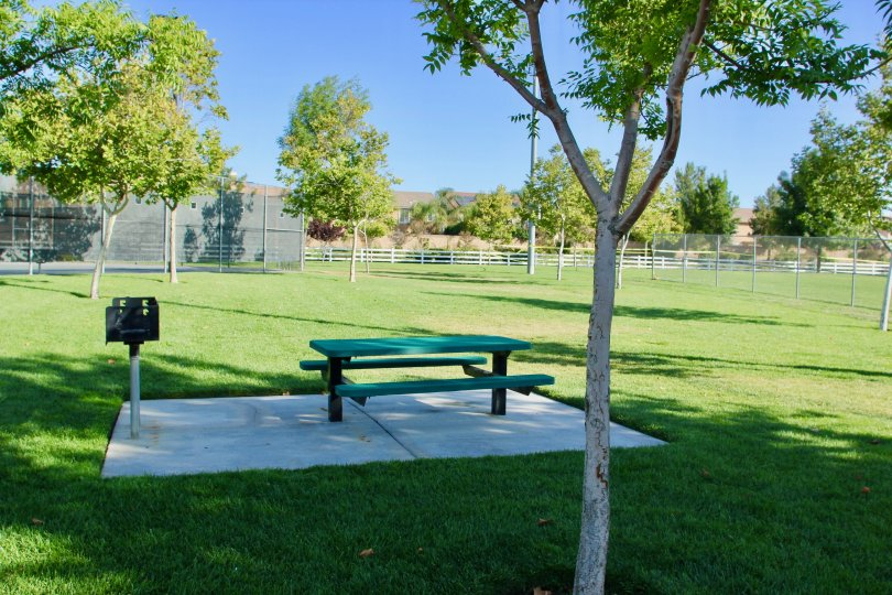 A small bench and a barbecue at a fenced in park of the Paseos at Crown Valley