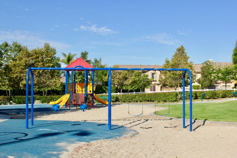 Fenced playground area with sand surface and colorful structures with multiple swings and slides