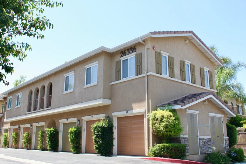 Beaufiul sunny day outside of Verona located in Murrieta, California. The unit appears to be an apartment complex with multiple garages on the bottom floor.