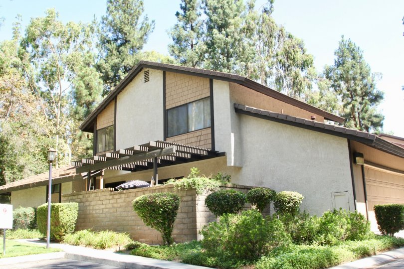 House with landscaped grounds and ample parking with garage nested between tall trees