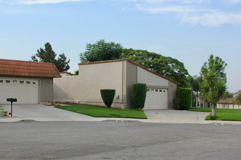 Ending coldesac features large garages and shrubs and trees between houses