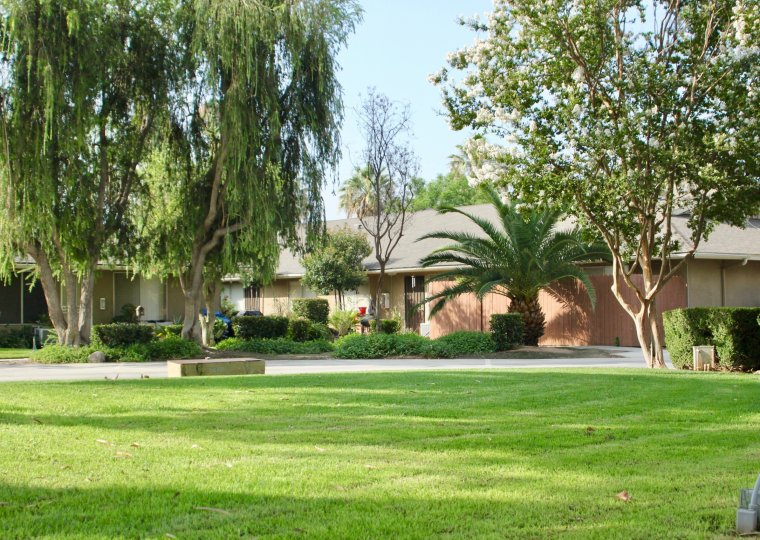 Reddish brown building in Holiday Park with green lawn and large trees in Riverside, CA