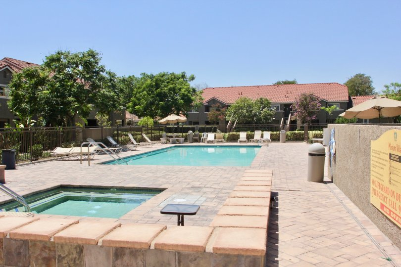 Sunny day at outdoor pool and hot tub area at Mission Villas community in Riverside, California