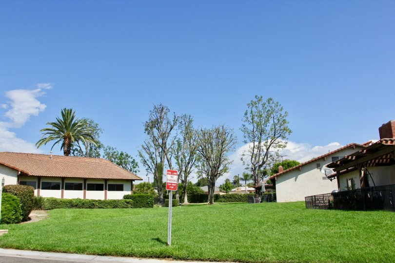 sunny grassy area of the Orangewood Villas with a no parking sign