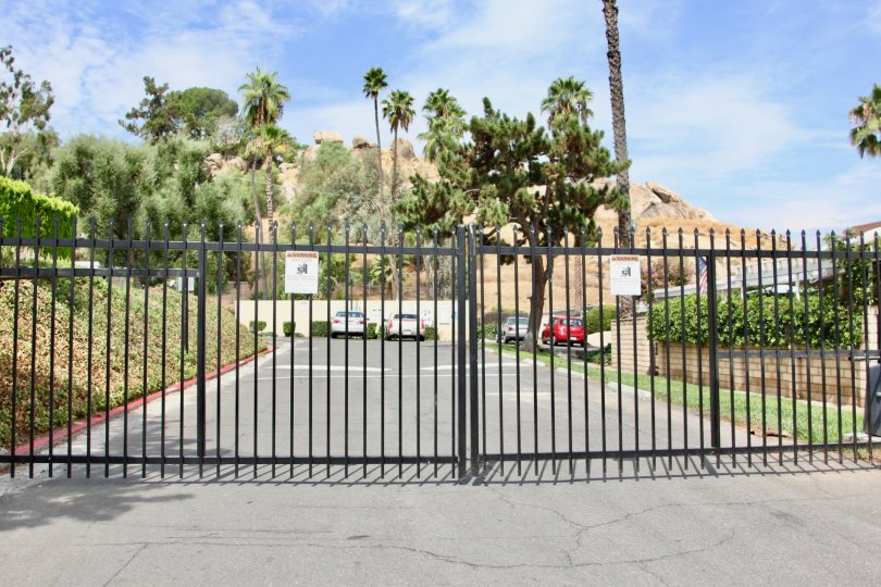 A bright morning at Rockledge Gardens with spacious car parking and a black closed gate.