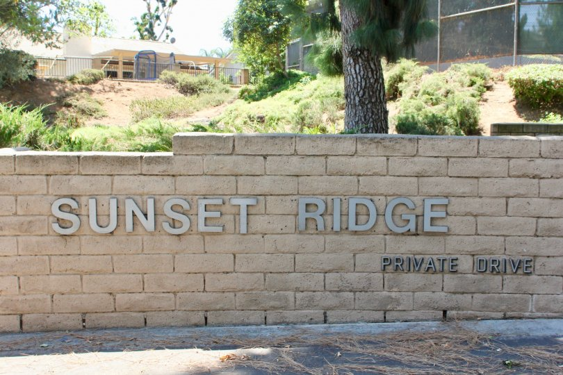 A bricked fence with the village name in Sunset Ridge community.