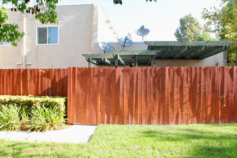 A backyard in neighborhood of University Grens in Riverside, California, with a brown fence and a building with satellite dishes.